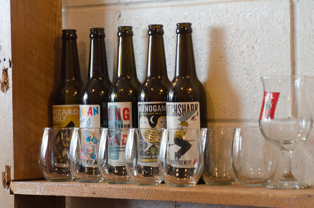 Four bottles of craft beer against a white brick wall, with stemless drinkware.