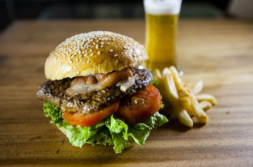 An overstuffed burger, filled with lettuce, tomato, and a thick patty, sits on a wooden table top next to a small heap of thick cut fries with a pint of lager in the background.